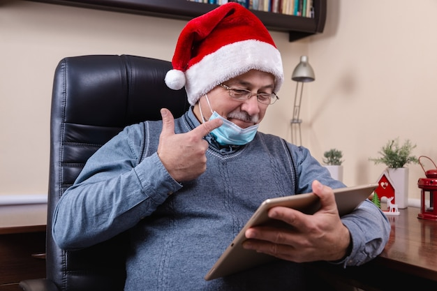 Christmas online congratulation. senior man in santa claus hat talks using tablet device for video call friends and childrens. the room is festively decorated. christmas during coronavirus.