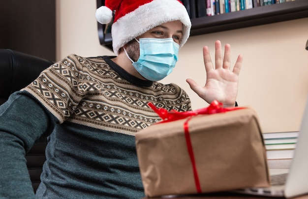 Christmas online congratulation. young man in santa claus hat and face mask gives a gift and talks using laptop for video call friends and childrens. christmas during coronavirus.