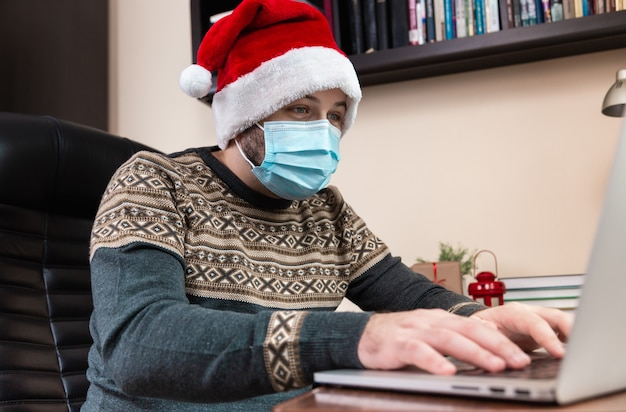 Christmas online congratulation. young man in santa claus hat and face mask talks using laptop for video call friends and childrens. christmas during coronavirus.