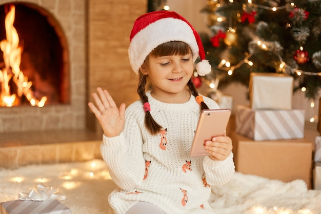 Christmas online, congratulations from home, smiling little girl using smart phone for video call. child talks to friends and parents, waves hands to greet, wearing santa hat, poses in festive room.