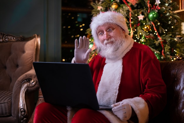 Christmas online congratulations from santa. santa claus using notebook laptop for distance