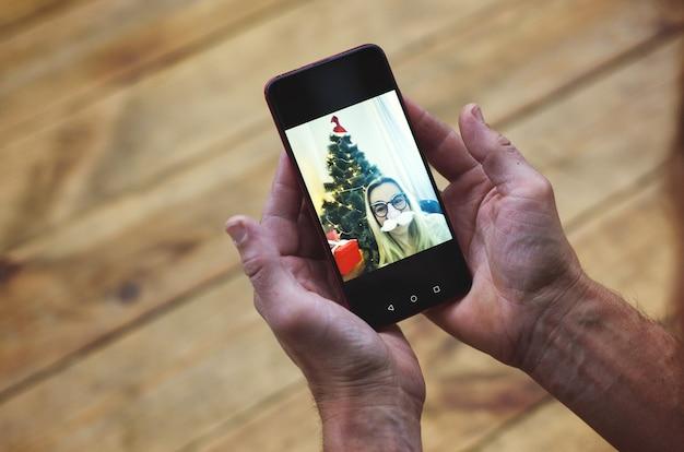 Рождественские онлайн-поздравления мужские руки держат смартфон и болтают с семьей