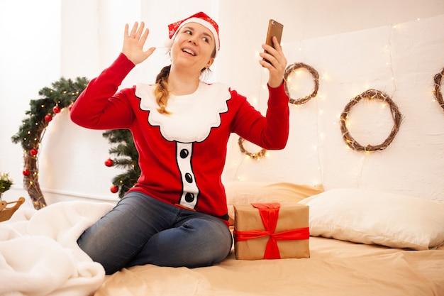 クリスマスオンライン休日おめでとうございます。ラッドハットをかぶった女性が電話を持ち、ビデオ通話で友人や家族とコミュニケーションをとる