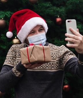 Рождественские онлайн-поздравления. портрет мужчины в шляпе санта-клауса и медицинской маске, дарит подарочную коробку с красной лентой, рождественскую елку боке на фоне