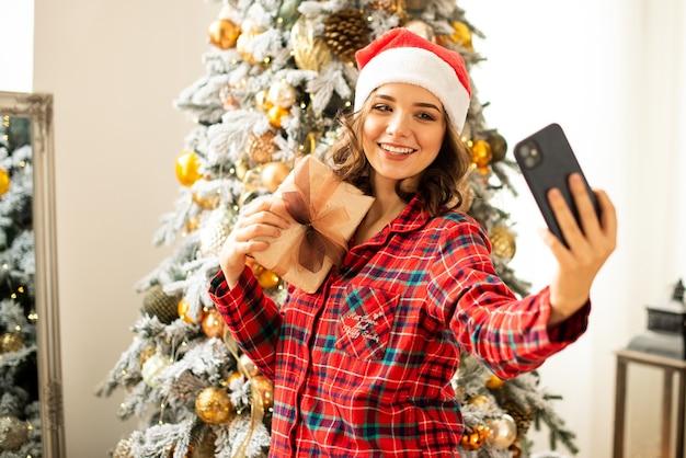 크리스마스 온라인 축하합니다. 화상 통화 친구와 부모를 위해 휴대 전화를 사용하여 웃는 유럽 갈색 머리 소녀.
