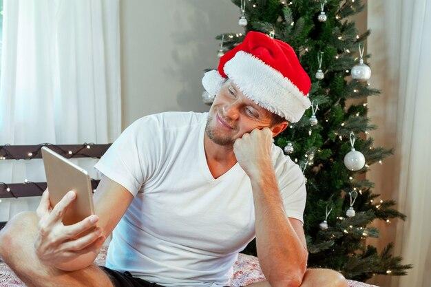 Рождественские онлайн-поздравления. улыбающийся человек, использующий компьютер (ноутбук) для видеозвонка друзей и родителей.