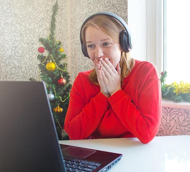 크리스마스 온라인 축하 놀란 소녀는 인터넷에서 친구들과 의사 소통합니다.