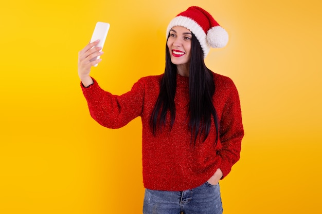 Christmas online congratulations. woman in santa hat using mobile tablet for video call friends and parents.