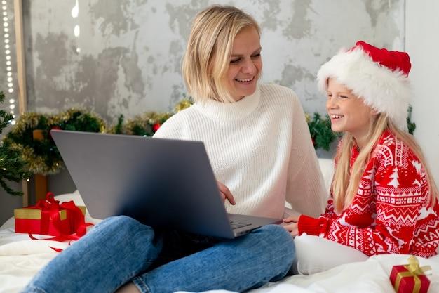 クリスマスオンライン家族おめでとうございます。ビデオ通話の友人や両親のためにモバイルタブレットを使用して笑顔のヨーロッパの金髪の母と娘