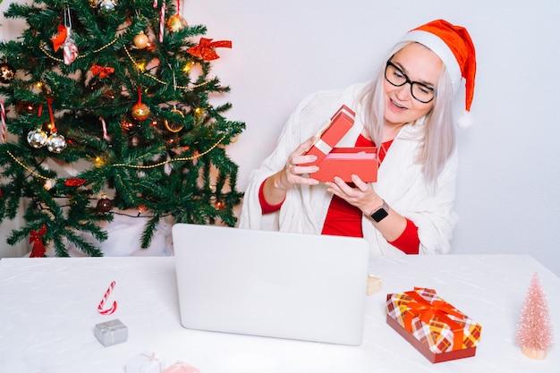 Рождественские онлайн-семейные поздравления. улыбающаяся девочка дома с помощью ноутбука
