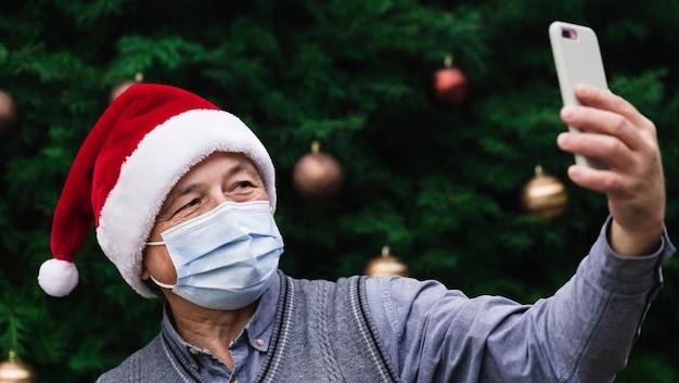 Рождественские онлайн-поздравления. крупным планом портрет старшего человека в шляпе санта-клауса и медицинской маске с эмоциями. на фоне елки. коронавирус пандемия