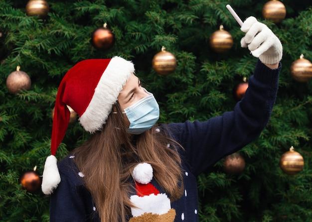 Рождественские онлайн-поздравления. крупным планом портрет женщины в шляпе санта-клауса и медицинской маске с эмоциями. на фоне елки. коронавирус пандемия