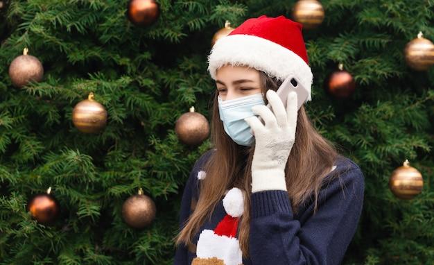 クリスマスのオンライン挨拶。感情を込めてサンタクロースの帽子と医療用マスクを身に着けている女性の肖像画を閉じます。クリスマスツリーを背景に。コロナウイルスパンデミック