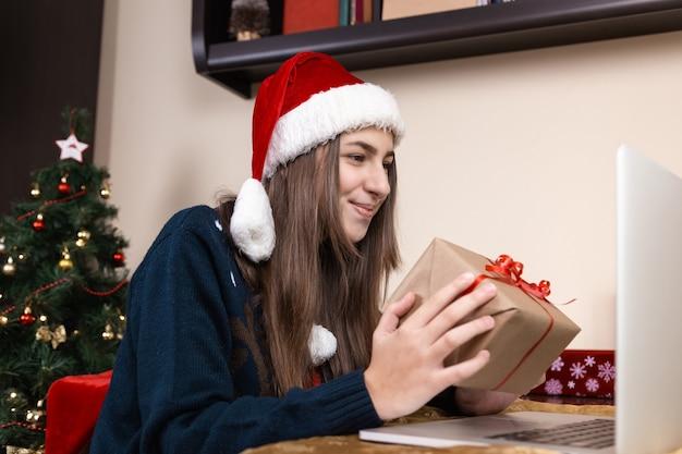 Рождественские онлайн-поздравления. девушка в шляпе санта-клауса разговаривает и дарит подарок, используя ноутбук для видеозвонков друзьям и родителям