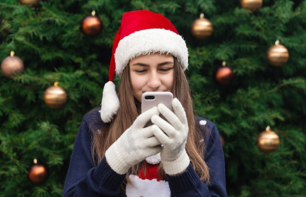 Christmas online greetings. girl in santa claus hat talks and using mobile smartphone for video call friends and parents. christmas during coronavirus.