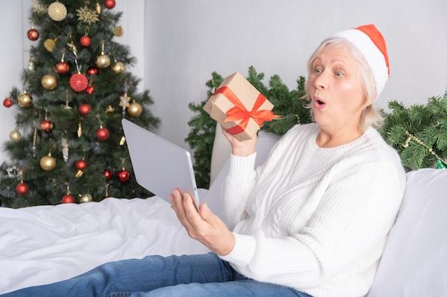 크리스마스 온라인 인사. 행복 한 흥분된 고위 여성 태블릿 침대에서 집에서 산타 모자에.