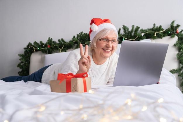 크리스마스 온라인 인사. 노트북과 함께 침대에서 집에서 산타 모자에 행복 한 고위 여성.