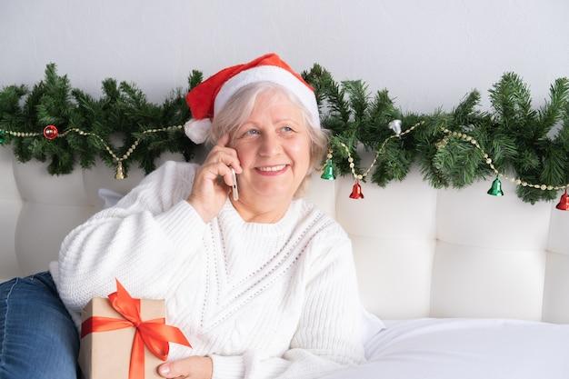 크리스마스 온라인 인사. 전화 침대에서 집에서 산타 모자에 행복 한 고위 여성.