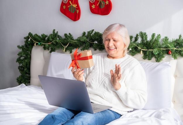 クリスマスのオンライン挨拶。ベッドで自宅でサンタの帽子をかぶった幸せな年配の女性。
