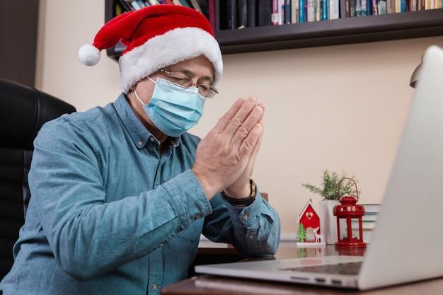 クリスマスのオンライン祈り。ビデオ通話の友人や子供たちのためにラップトップを使用してサンタクロースの帽子の祈りの年配の男性。部屋はお祝いに飾られています。コロナウイルス中のクリスマス。