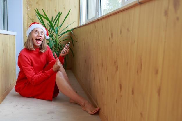 크리스마스 온라인 쇼핑 행복한 여자가 온라인으로 주문하고 전화를 통해 신용 카드로 지불합니다.