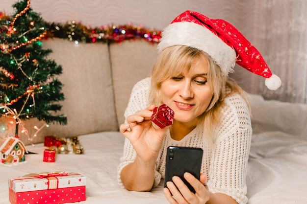 Christmas online shopping. female buyer makes order on mobile phone. woman buy presents, prepare to xmas, gift box in hand. winter holidays sales.