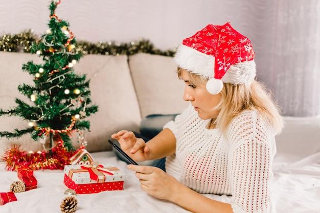 Рождественские покупки в интернете. покупатель-женщина делает заказ на распродажах mobile phone.ys.