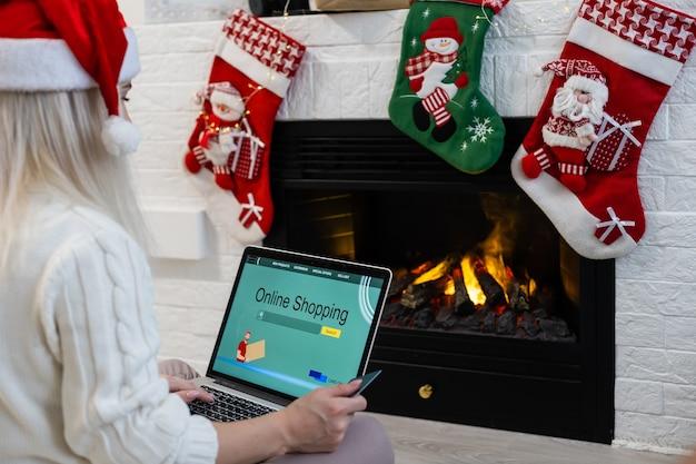 Рождественские покупки в интернете. покупатель женского пола с ноутбуком, копией пространства на экране. женщина покупает подарки, готовится к рождеству, сидя среди подарочных коробок и пакетов. распродажа на зимние каникулы