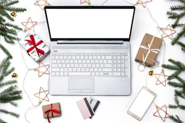クリスマスのオンラインショッピングフラットが横たわっていた。オープンラップトップ、クレジットカード、赤いリボンで結ばれたギフトボックス、緑のモミの枝、星の花輪