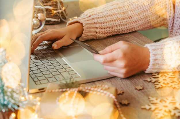 테이블에 선물, 노트북, 신용 카드 및 새해 장식을 위한 크리스마스 온라인 쇼핑