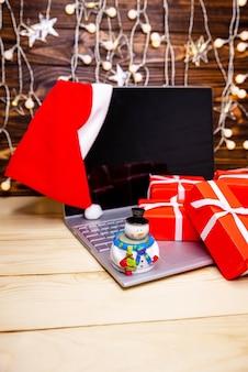 Рождественские покупки в интернете. подарочные коробки над портативным компьютером