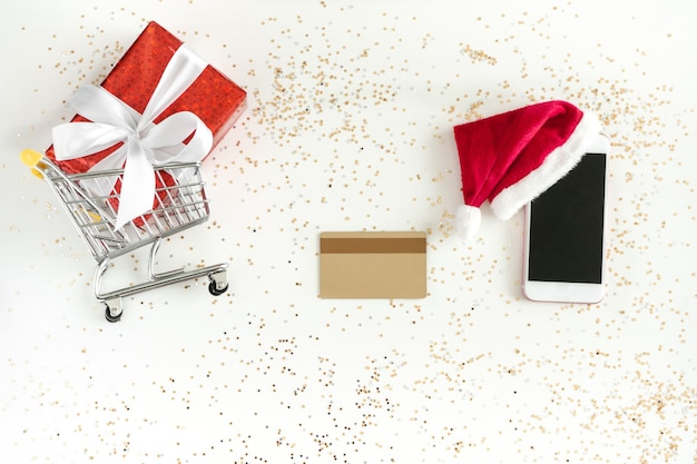Christmas online shopping. mini shopping car , cellular, credit card and gift box, top view