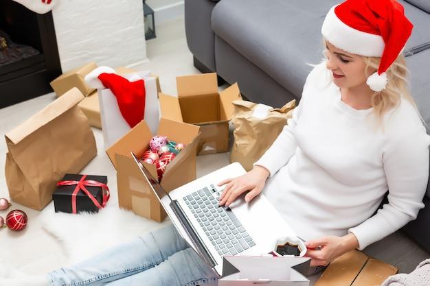 크리스마스 온라인 쇼핑 상위 뷰입니다. 노트북을 가진 여성 구매자, 화면에 공간을 복사합니다. 여자는 커피를 마시고, 선물을 사고, 크리스마스 이브를 준비하고, 선물 상자와 패키지 사이에 앉아 있습니다. 겨울방학 세일
