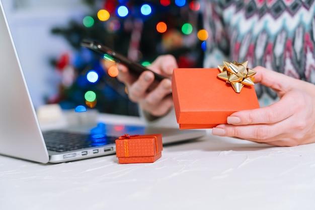 크리스마스 온라인 쇼핑. 여자는 선물을 구입하고, 크리스마스를 준비하고, 쇼핑 카트와 선물 상자 사이에서. 겨울 휴가 메리 크리스마스 겨울 휴가 판매 개념. 선택적 초점.