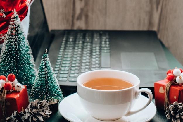 크리스마스 온라인 쇼핑, 일 및 교육. 테이블에 새 해 장식입니다. 집에 있는 노트북 컴퓨터. 겨울방학 세일. 선물 상자, 크리스마스 트리. 가랜드 라이트