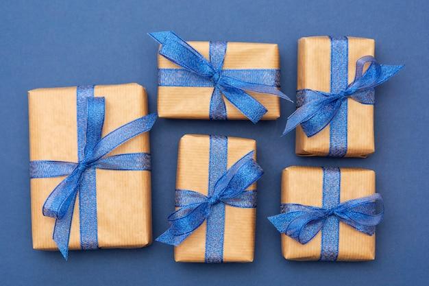 Рождество или подарки на день рождения, крафт-бумага обернутая подарочные коробки на синем, плоские лежал.