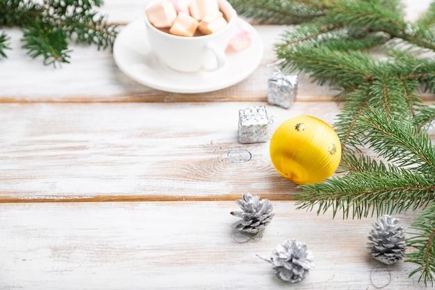 크리스마스 또는 구성. 장식, 공, 콘, 전나무와 가문비 나무 가지, 흰색 나무 테이블에 커피 한잔.