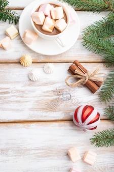 크리스마스 또는 구성. 장식, 상자, 공, 계피, 리본, 전나무 및 가문비 나무 가지, 흰색 나무 테이블에 커피 한잔. 평면도.