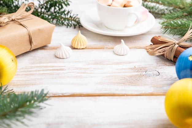 크리스마스 또는 구성. 장식, 상자, 공, 계피, 리본, 전나무 및 가문비 나무 가지, 흰색 나무 테이블에 커피 한잔.