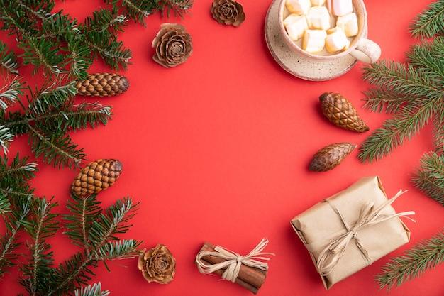 크리스마스 또는 구성. 장식, 상자, 계피, 콘, 전나무 및 가문비 나무 가지, 빨간 종이에 커피 한잔. 평면도.
