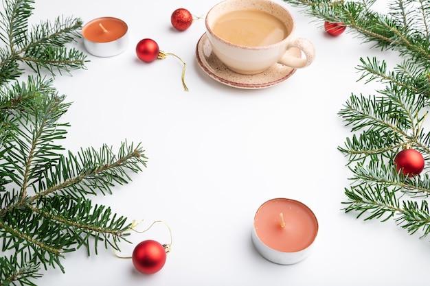 크리스마스 또는 구성. 장식, 빨간 공, 전나무 및 가문비 나무 가지, 커피 한잔, 흰 종이에 양초