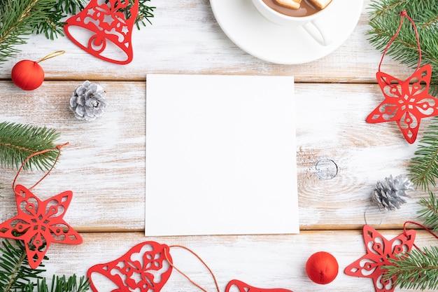 크리스마스 또는 구성, 템플릿. 장식, 붉은 별, 종소리, 콘, 전나무 및 가문비 나무 가지, 흰색 나무 테이블에 커피 한잔. 평면도.