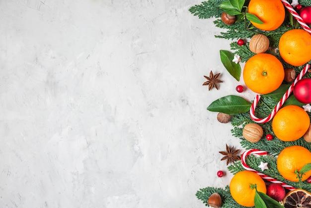 Рождественские или счастливые новогодние композиции из мандаринов, еловых веток, рождественских пищевых украшений на бетонном фоне. плоская планировка. вид сверху с копией пространства