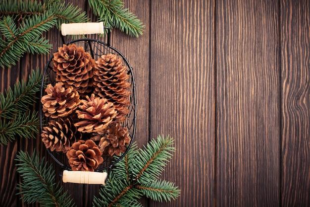 크리스마스 또는 새 해 배경입니다. 짙은 갈색 나무 배경에 전나무 가지, 크리스마스 트리 장난감, 별, 눈송이, 원뿔. 선택적 초점입니다. 평면도. 복사 공간