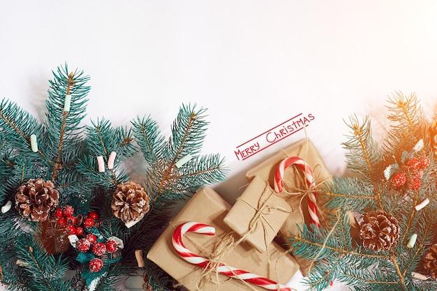 Рождество или новый год фон ёлочные ветки подарки украшение на белом фоне солнечные блики