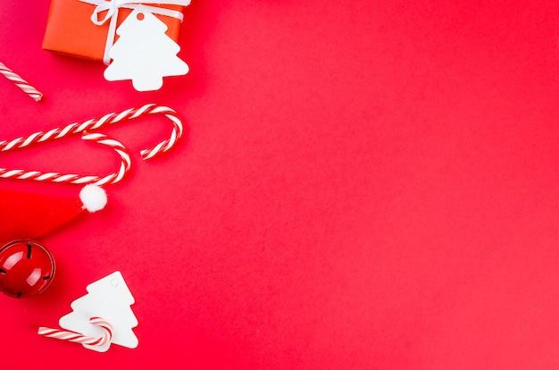 クリスマスまたは新年の背景ギフトボックスキャンディーキャラメルケーキと赤い背景の装飾