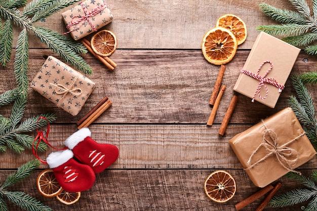 크리스마스 또는 새해 배경에는 전나무 가지, 크리스마스 공, 선물 상자, 나무 눈송이, 별들이 어두운 나무 배경에 있습니다. 텍스트를 위한 장소