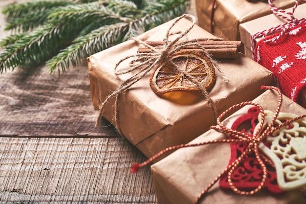Рождество или новогодний фон с еловыми ветками, рождественскими шарами, подарочной коробкой, деревянными снежинками и звездами на темном деревянном фоне. место для текста