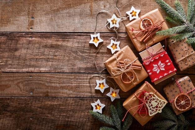 크리스마스 또는 새해 배경에는 전나무 가지, 화환, 크리스마스 공, 선물 상자, 나무 눈송이 및 어두운 나무 배경에 별이 있습니다. 텍스트를 위한 장소