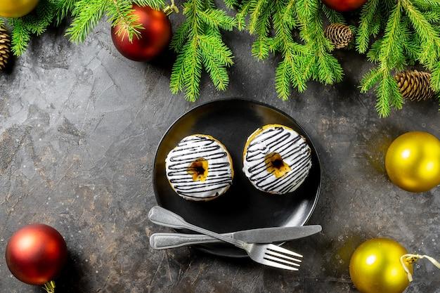 モミの木、バンプと黒いプレート、ドーナツとクリスマスや新年の背景